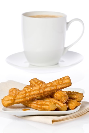 Churros with dulce de leche on a small plate, and a cup of hot chocolate against a white background.
