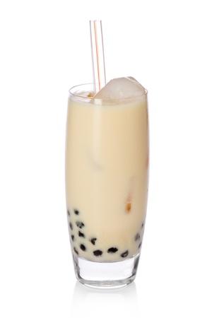 タピオカ真珠と藁の上に白い背景と甘いバナナ牛乳お茶のガラス。 写真素材