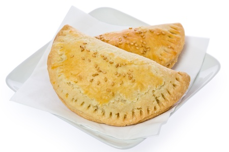 A couple of empanadas on a small square plate against a white background. Imagens