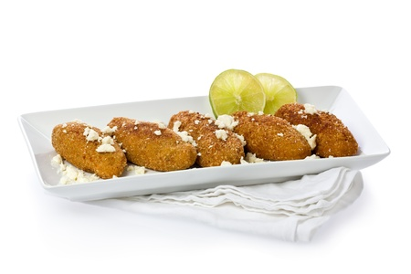 crumbly: Several fried empanadas made from plantains and topped with crumbly cheese on a white plate.