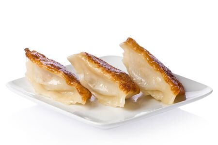 potstickers: Three pork potstickers on a small white plate against a white background.