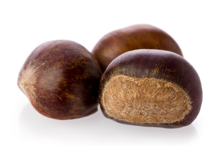 Close-up of three chestnuts against a white background. Imagens