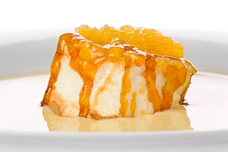 Floating Island Dessert: Meringue topped with caramel and a fresh slice of orange floating on vanilla custard on a white plate