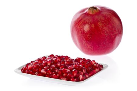 Pomegranate seeds on a white plate with whole pomegranate in the background.