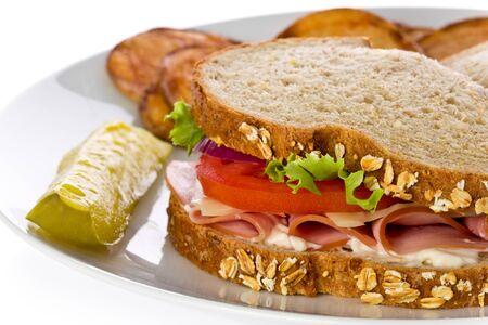 ham sandwich: Panino al prosciutto con il formaggio svizzero, lattuga e pomodori, con patatine fritte fatte in casa su un piatto bianco.
