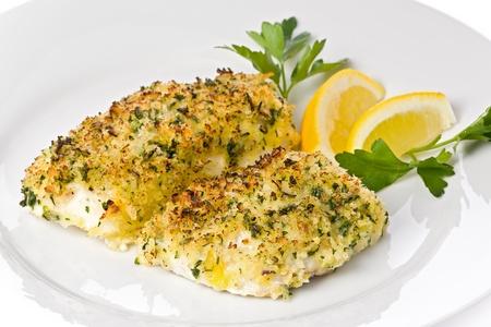 レモン スライスとパセリを添え白い皿にパン粉を焼いたタラ。