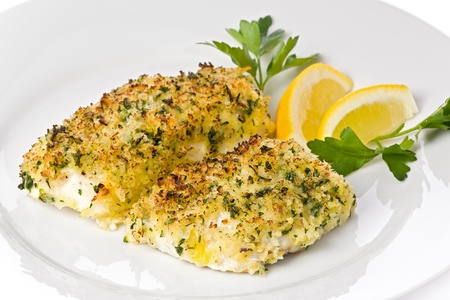 Baked cod with breadcrumbs on a white plate garnished with lemon slices and parsley.