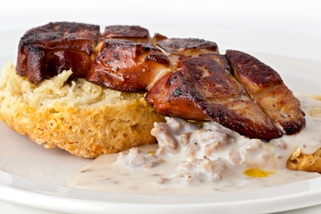 seared: Pan seared foie gras with biscuits and gravy on a white plate. Stock Photo