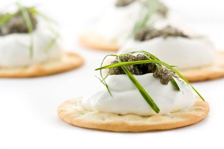 Several canapes with caviar and creme fraiche against a white background.