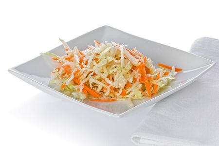 side salad: Coleslaw with simple vinaigrette on a white plate with napkin.