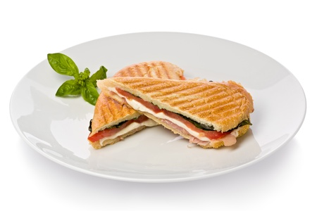 Panini sandwich with prosciutto, mozzarella cheese and basil on white plate.
