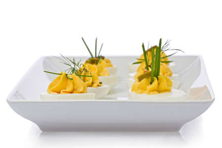 deviled eggs: Several deviled eggs on a white plate.