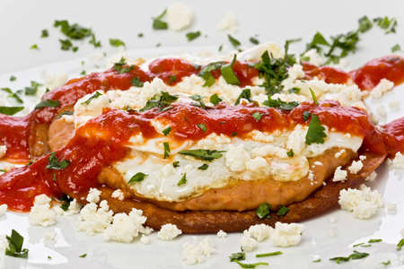 corn tortilla: Fried corn tortilla with refried beans, fried egg, crumbly cheese, and topped with a spicy chili sauce. Stock Photo