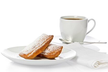 Two New Orleans style beignets with a cup of coffee against a white background