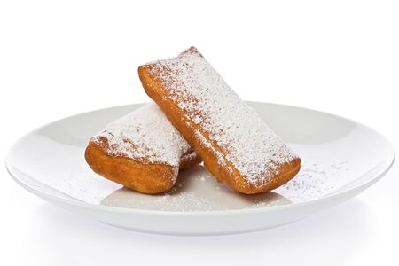 powdered sugar: Two New Orleans style beignets on a white plate against a white background