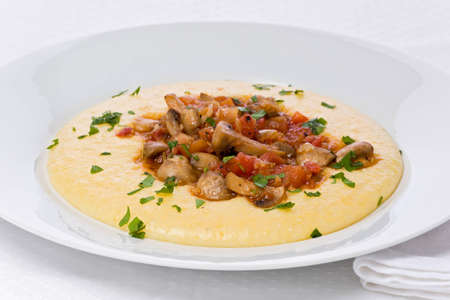 polenta: Winter mushroom stew with tomatoes and white wine on a bed of creamy polenta with parmesan.