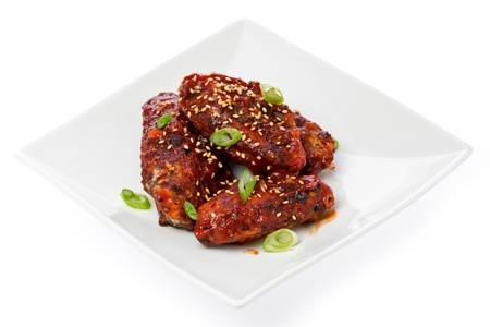 Korean-style fried chicken wings with spicy sauce on small square plate. Imagens
