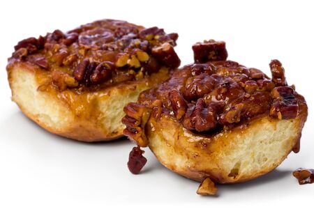 pecans: Homemade sticky buns against a white background.