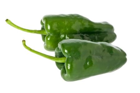 Twee hele groene poblano paprika's tegen een witte achtergrond.