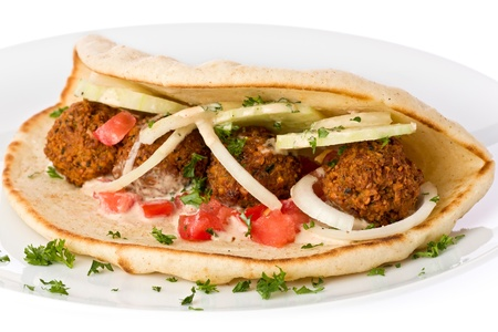falafel: Homemade chickpea falafel on flatbread with tomato, onions, cucumber slices with tahini sauce on a white plate.