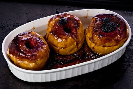 blackberry: Baked apples with blackberries in a casserole dish on a baking tray.