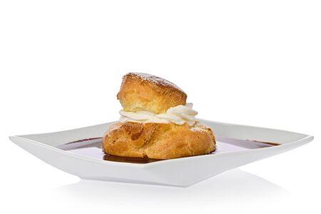 cream puff: Cream puff with raspberry filling in a chocolate sauce on a square dessert plate.