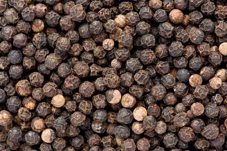 Background texture of whole, dried, black peppercorns. 版權商用圖片
