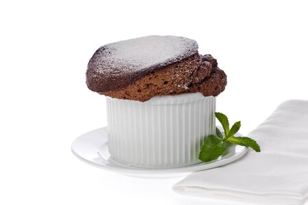A single small chocolate souffle dusted with powdered sugar against a white background. Stock Photo