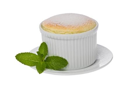 Single small vanilla souffle in a white ramekin against a white background.