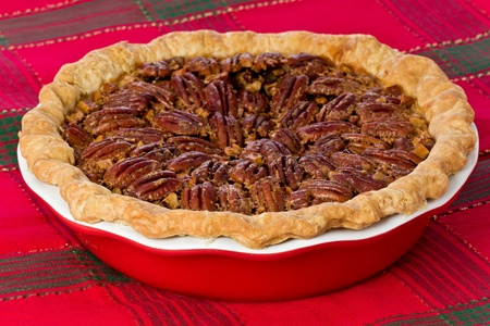 Whole pecan pie on a red and green tablecloth. Stock Photo