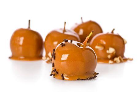 Several mini caramel apples against a white background.