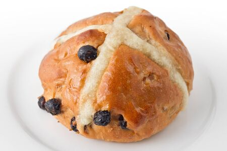 Traditional hot cross bun on white plate.