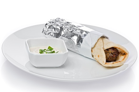 Kofte kebab in flatbread with garlic sauce on the side on a white plate against a white background  Фото со стока