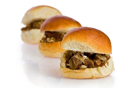 sliders: Three cuban shredded beef, or vaca frita, sliders against a white background.