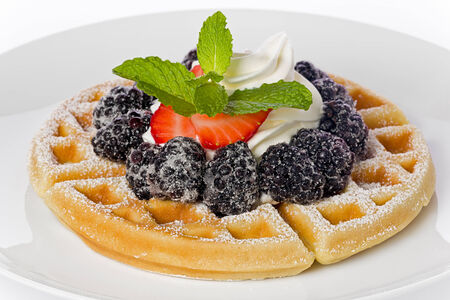Belgian waffle with fresh whipped cream and topped with blackberries, strawberries and a sprig of mint, on a white plate.
