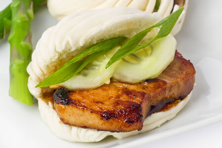 hoisin sauce: Braised pork belly slices on chinese steamed buns, with hoisin sauce and green asparagus. Stock Photo