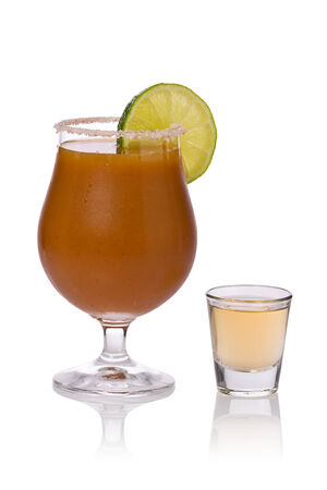chaser: Sangrita chaser in a glass with a slice of lime next to a shot glass of tequila against a white background.