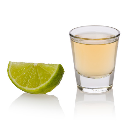 A shot glass of tequila and a slice of lime against a white background.