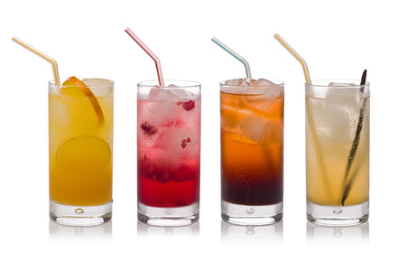 carbonated: Four glasses of cold, fresh, homemade sodas with ice and drinking straws against a white background. Flavors include orange, raspberry, cola and vanilla ginger. Stock Photo