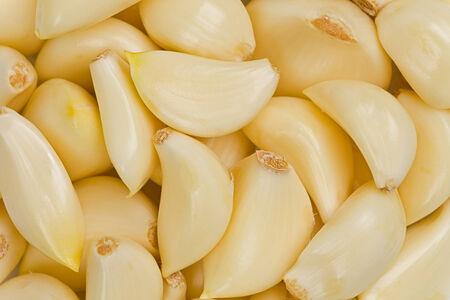 background texture of peeled whole garlic cloves. Фото со стока