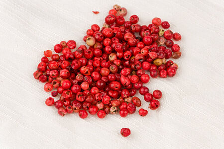 A small pile of pink peppercorns on a textured cloth.