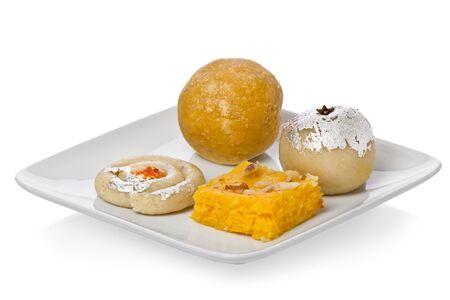 Diverse Indiase snoep op een kleine witte plaat tegen een witte achtergrond.