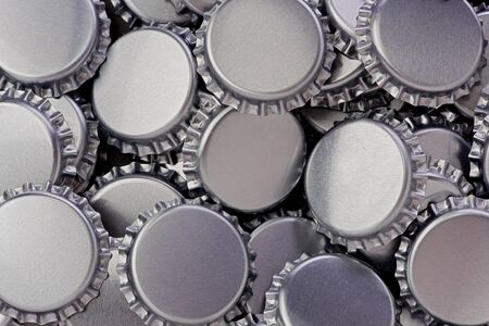 Background texture of several silver bottle caps. Фото со стока