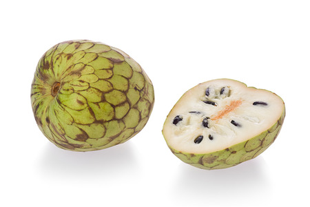 custard apple: One whole, and one sliced Cherimoya, or custard apple, against a white background.
