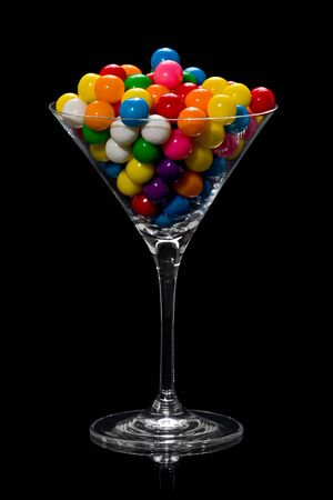 A martini glass full of gumballs of different colors against a black background.