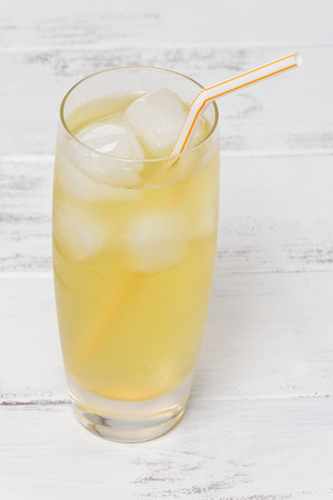 Glass of iced green tea with a straw, on a white, painted wood background. Stok Fotoğraf