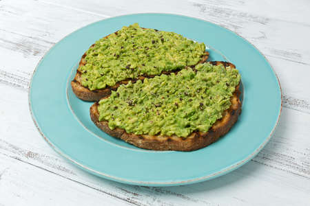 Two slices of avocado toast with cracked black pepper on a blue plate.