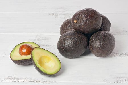 One sliced, and several whole avocados on a white painted wood background.