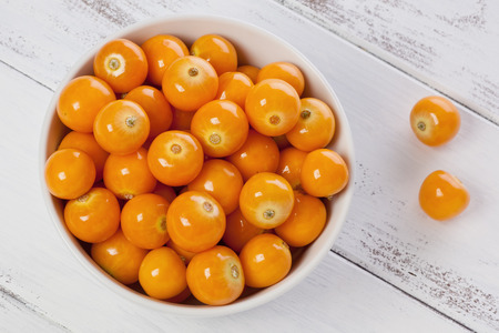 A small bowl of Cape Gooseberries, or goldenberries, on a painted white background. Stockfoto