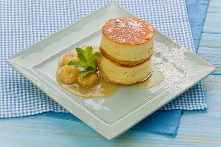 Two japanese style pancakes with banana-rum sauce on a square plate, garnished with mint leaves. Stock Photo